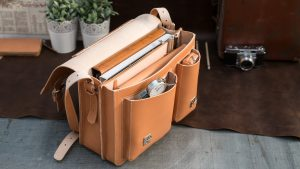 Tan leather satchel with asymmetric front pockets.